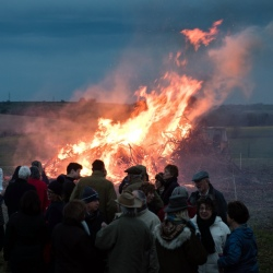 Celebrating HM the Queen's 90th Birthday beacon at Hartley Hill. 30 or so people gathered together facing the camera with drinks in hands and the bonfire burning behind them